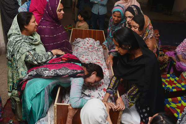 Family members of a victim Monday in Lahore, Pakistan, where a suicide bombing killed dozens. Credit Arif Ali/Agence France-Presse — Getty Images