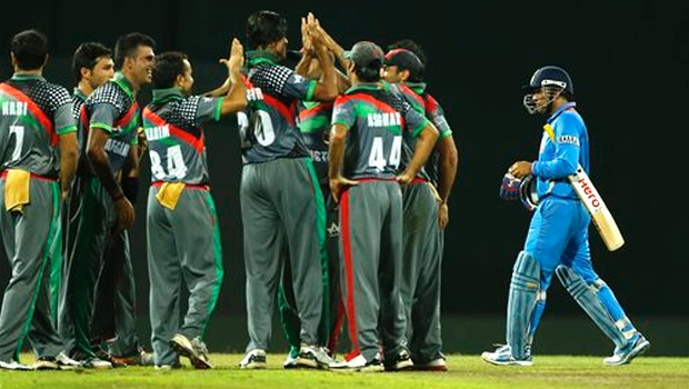 Afghanistan team mates celebrate the wicket of Virender Sehwag, right. AP