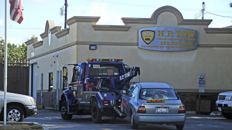 A car is towed into the lot at H.P. Tow in Huntington Park earlier this year. A federal grand jury has indicted one of the company's owners. (Christina House / Los Angeles Times)