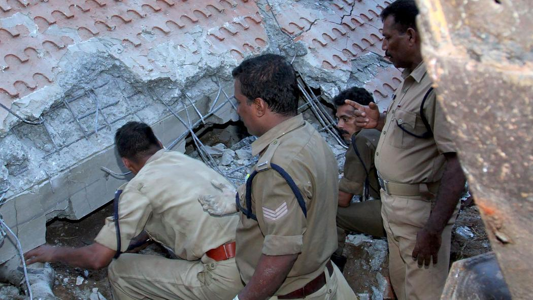 Indian officials gather beside a collapsed building as they try to rescue survivors after an explosion and fire at The Puttingal Devi Temple in Paravur early April 10, 2016.