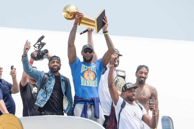 LeBron James hoists the Larry O'Brien Trophy while stepping off the Cavaliers plane after Cleveland returned home from winning the NBA Finals.