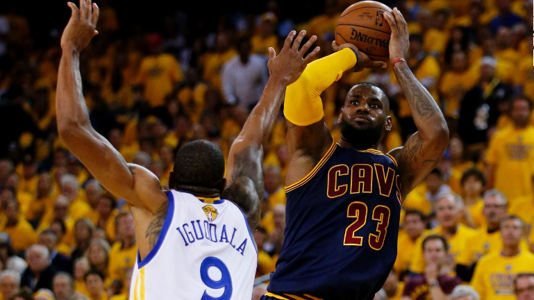 Andre Iguodala of the Warriors contests a shot by LeBron James of the Cavaliers.