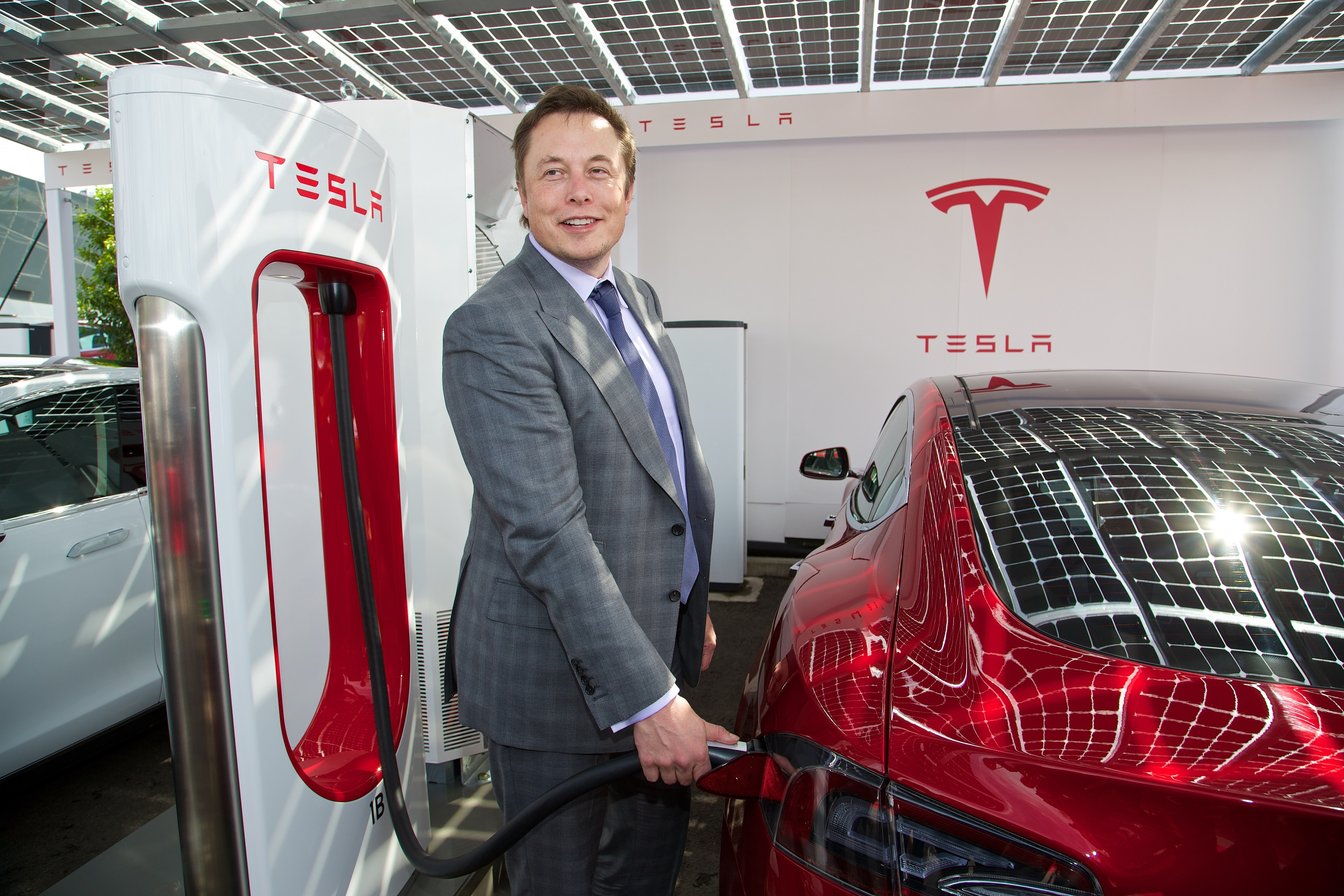 LONDON, ENGLAND - Saturday, June 7, 2014: CEO & Chief Product Architect Elon Musk plugs in a Supercharger to a right-hand drive Model S at the UK launch of Tesla Motors' Model S electric car at the Crystal.
