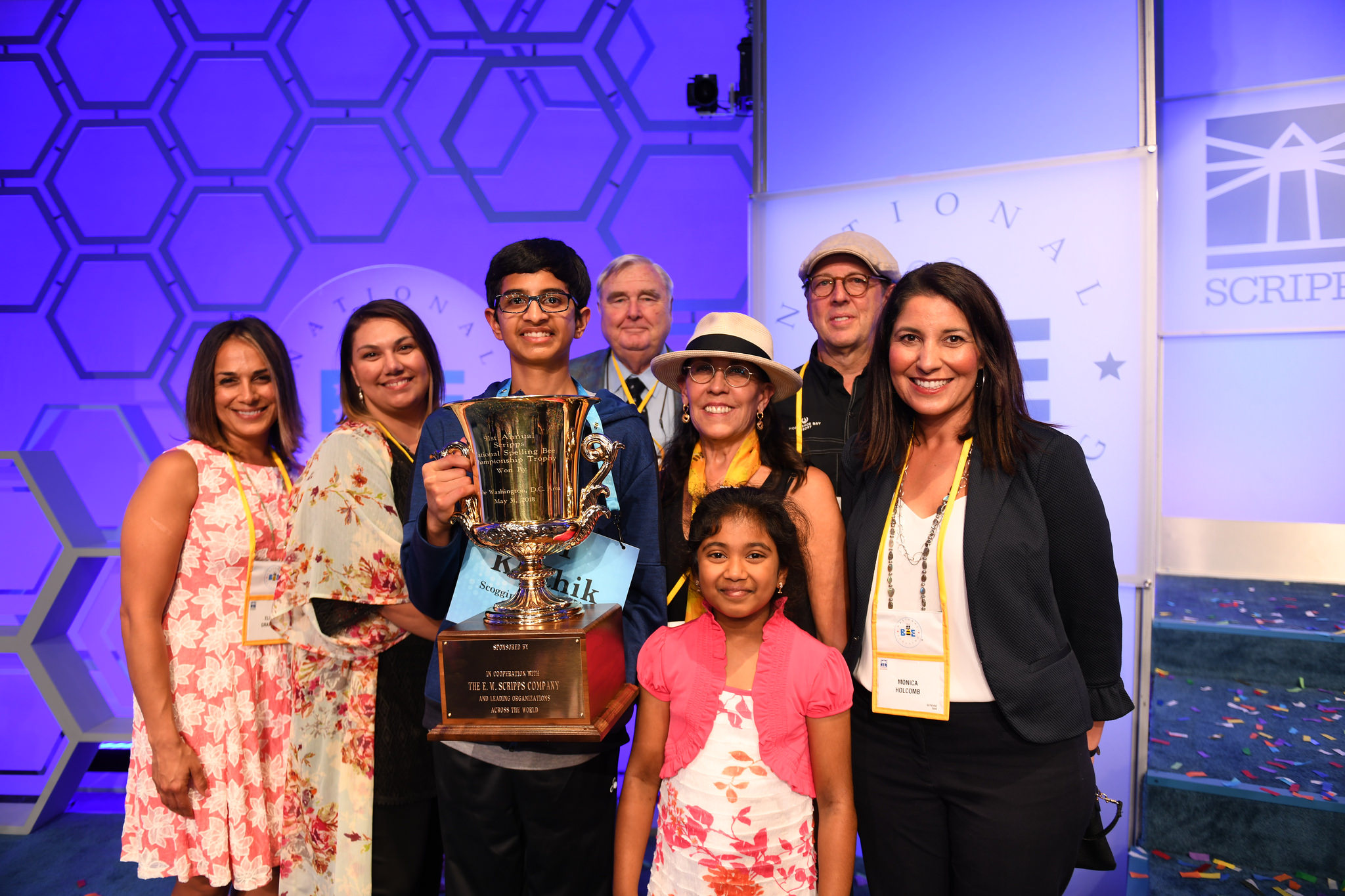 Karthik Nemmani surrounded by family, holding his Championship Trophy (Photo: Scripps Spelling Bee)